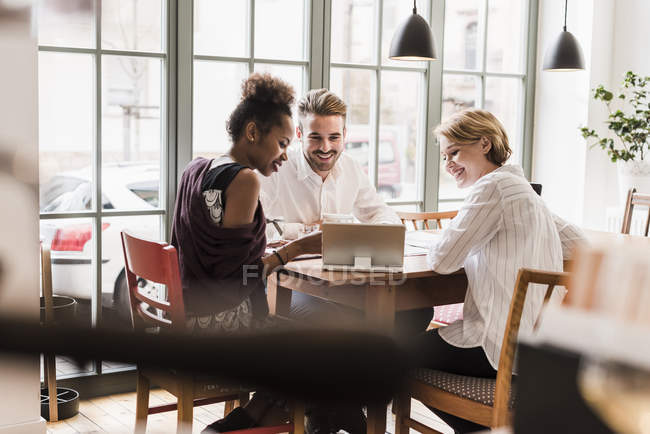 Three young people using tablet in a cafe — Stock Photo