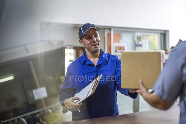 Delivery man handing over cardboard box — Stock Photo