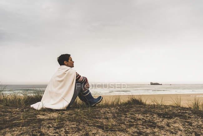 Mulher sentada na costa envolta em cobertor — Fotografia de Stock