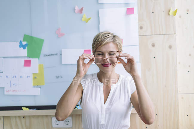 Smiling businesswoman in front of whiteboard in modern office — Stock Photo