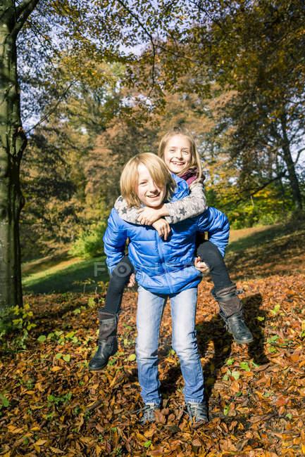 Retrato de niño dando a su hermana un paseo en cerdito en otoño - foto de stock