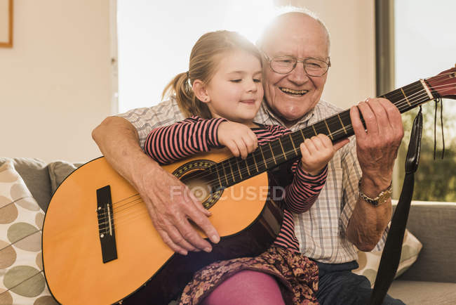 Grandfather and granddaughter playing guitar together — Stock Photo