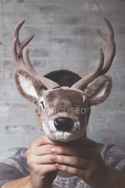 Young man holding artificial deer head  in front of his face — Stock Photo