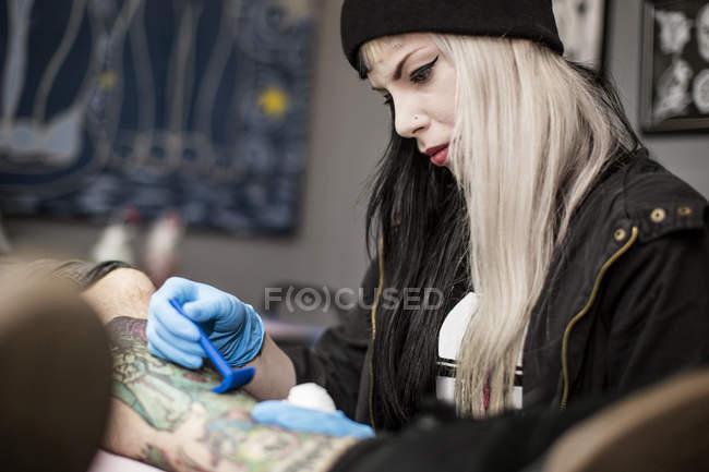 Tatouage femme artiste rasage jambe avant tatouage — Photo de stock