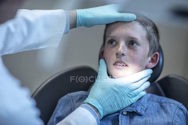 Garçon nerveux avec appareil dentaire en chirurgie dentaire regardant orthodontiste — Photo de stock