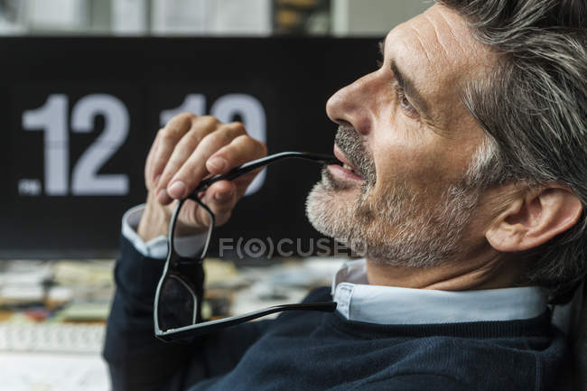 Pensativo maduro homem segurando óculos — Fotografia de Stock