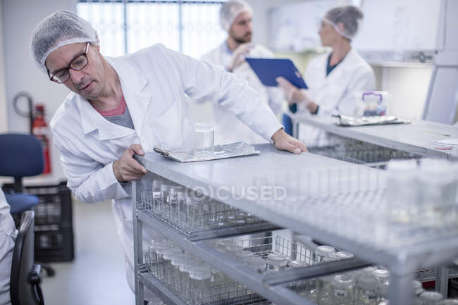 Scientists working in lab wearing protective clothing — Stock Photo