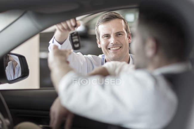 Car dealer giving key to man sitting in car — Stock Photo