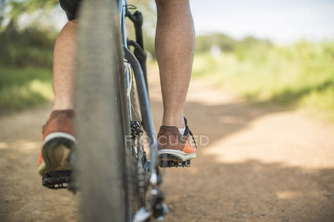 Young man mountain biking in nature, low section, rear view — Stock Photo