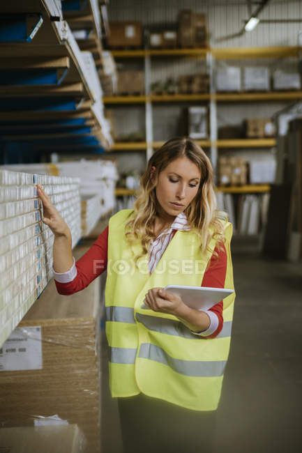 Woman in warehouse supervising stock — Stock Photo