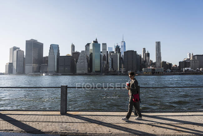 Business woman using smartphone in front of Manhattan skyline, USA, New York — стоковое фото