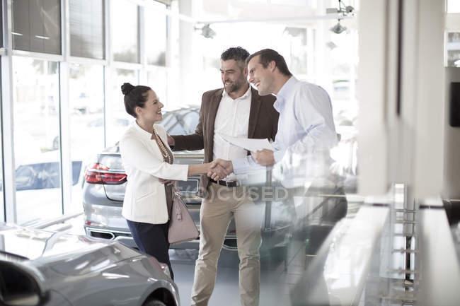 Concessionario auto stringendo la mano con la donna in concessionaria auto — Foto stock