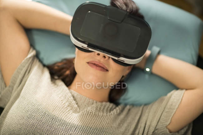 Young woman using Virtual Reality Glasses at home — Stock Photo