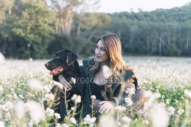 Young woman and her dog in field of flowers — Stock Photo