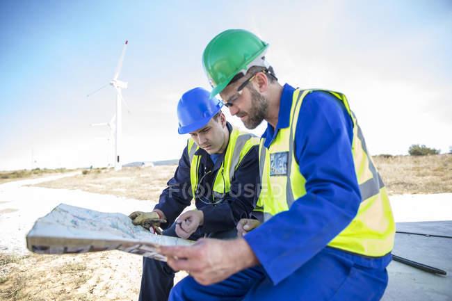 Les ingénieurs du parc éolien regardent la carte — Photo de stock