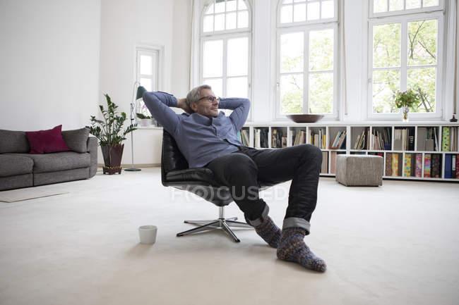 Entspannte reifer Mann sitzt im Stuhl zu Hause — Stockfoto