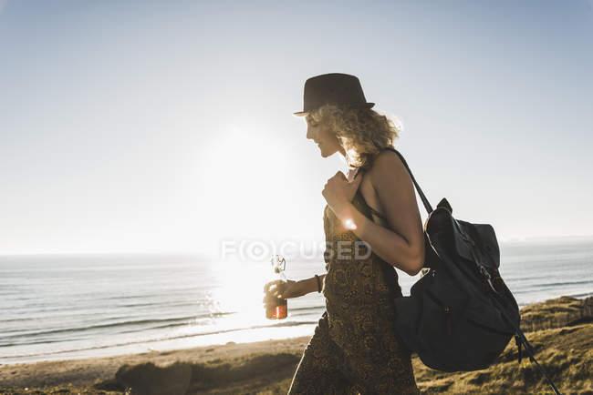 Blonde Teenager-Mädchen mit Rucksack und Getränkeindustrie zu Fuß am Meer in der Abenddämmerung — Stockfoto