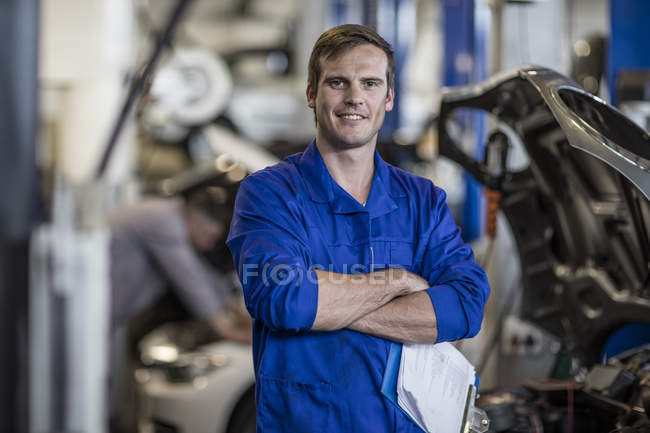 Confident car mechanic in repair garage — Stock Photo