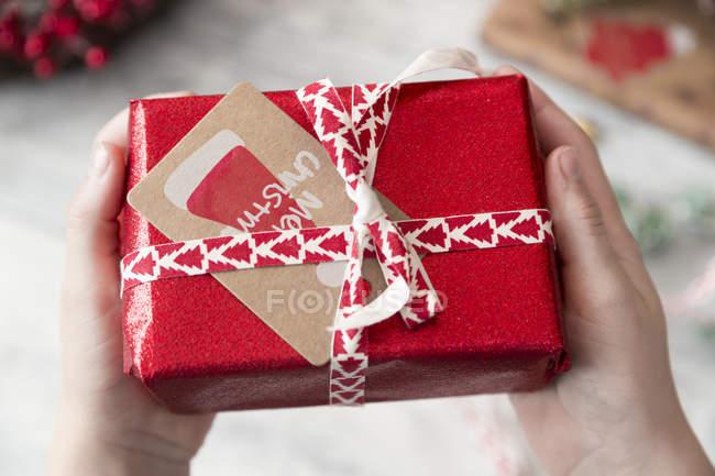 Mädchen halten eingewickelt Weihnachtsgeschenk mit Karte, Nahaufnahme — Stockfoto