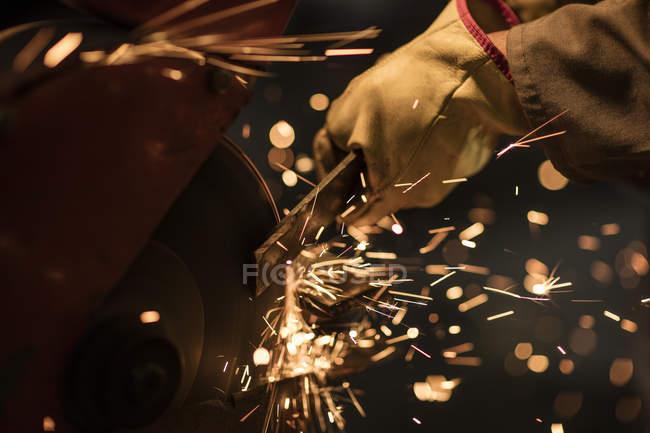 Metallarbeiter mit Schleifmaschine in Fabrikhalle — Stockfoto