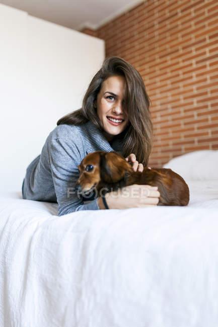 Giovane attraente donna caucasica coccole cane sul letto — Foto stock