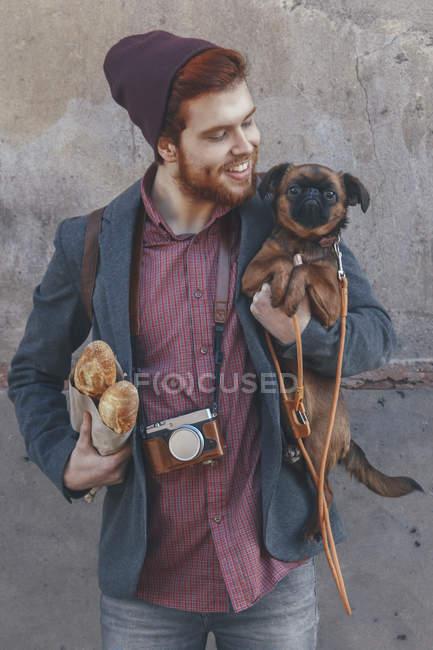 Sorridente giovane uomo che tiene il cane — Foto stock