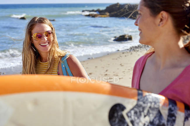 Two happy women carrying surfboards on the beach — Stock Photo