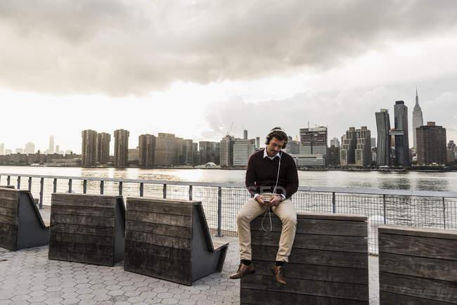 Giovane uomo con cuffie e cellulare seduto a East River, New York, Stati Uniti — Foto stock