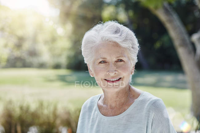Portrait of smiling senior woman in park — Stock Photo