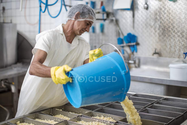 Cheese factory worker pouring curd into containers — Stock Photo