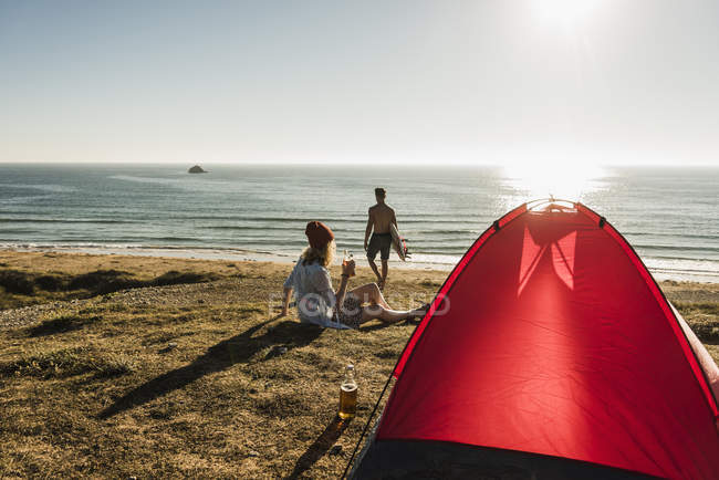 Young couple camping at seaside, sunset seascape and red tent view — Stock Photo