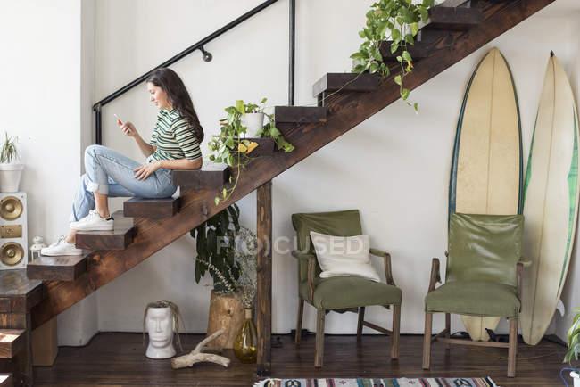 Молода жінка, сидячи на сходах горищі, дивлячись на мобільний телефон — стокове фото