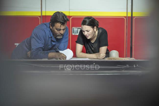Mecânica, trabalhando na oficina de brigada de incêndio, lista de verificação de leitura — Fotografia de Stock