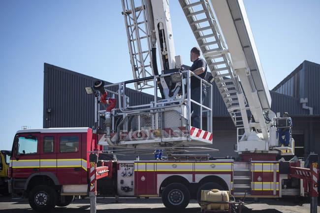 Mechaniker warten Feuerwehrauto im Freien — Stockfoto