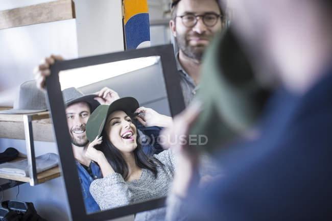 Amici felici in negozio cercando sui cappelli — Foto stock
