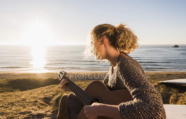 Грав на гітарі в приморському у вечірні сутінки дівчинки-підлітка — стокове фото