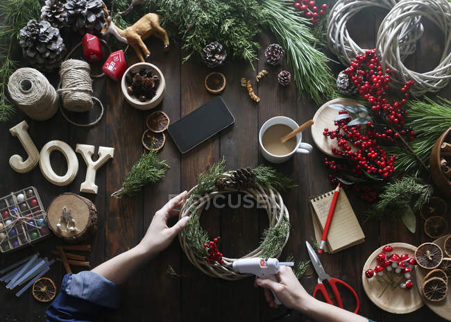 Woman using glue gun for decorating Advent wreath, partial view — Stock Photo