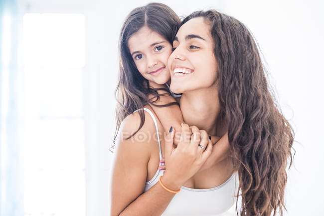 Happy teenage girl carrying her little sister at home — Stock Photo