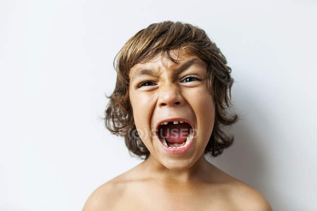 Portrait of screaming little boy with tooth gap in front of white background — Stock Photo