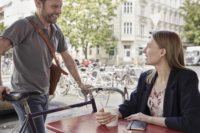 Homme souriant avec vélo arrivant à un café trottoir regardant femme — Photo de stock