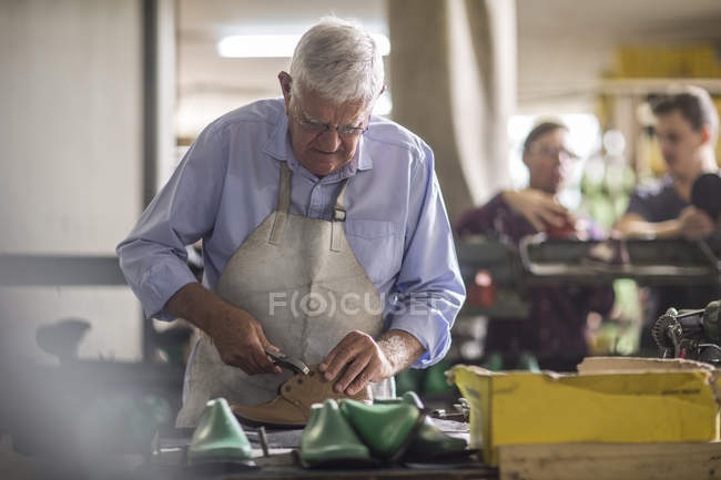 Shoemaker working on shoe in workshop, people on background — Stock Photo