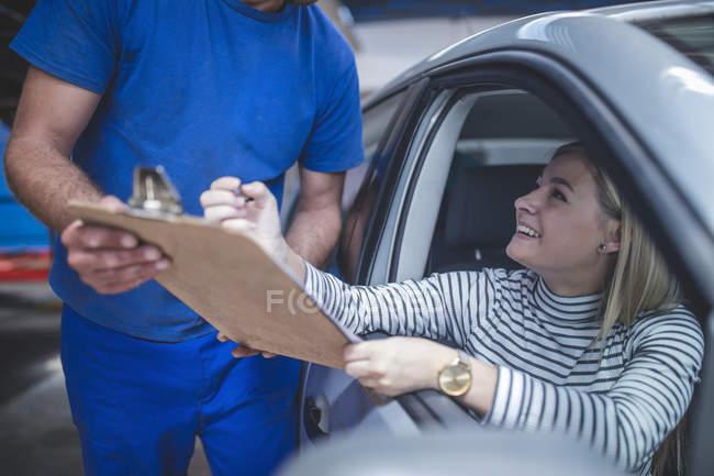 Sorrindo ao cliente feminino no carro preenche formulário na área de transferência no workshop — Fotografia de Stock