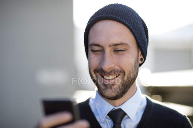 Young man wearing beanie holding cell phone — Stock Photo
