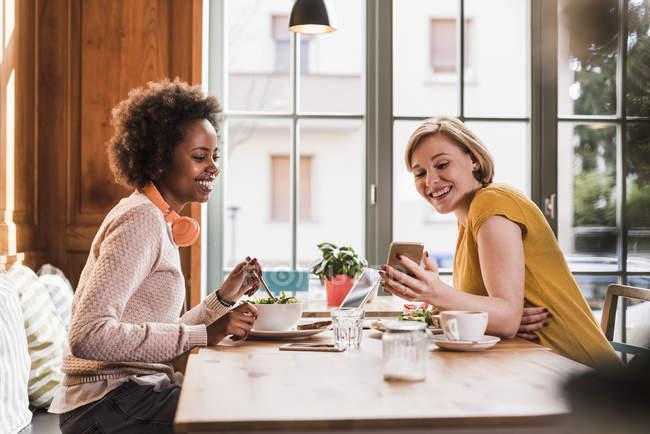 Duas jovens mulheres com telefone celular reunidas em um café — Fotografia de Stock