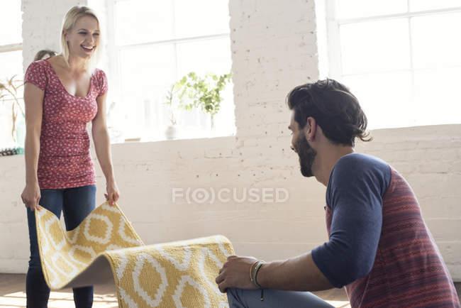 Молодая пара, поместив ковер в чердак — стоковое фото