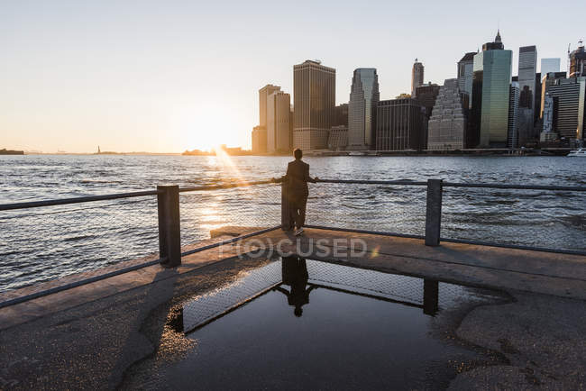 Donna appoggiata alla ringhiera e guardando il tramonto, USA, New York — Foto stock
