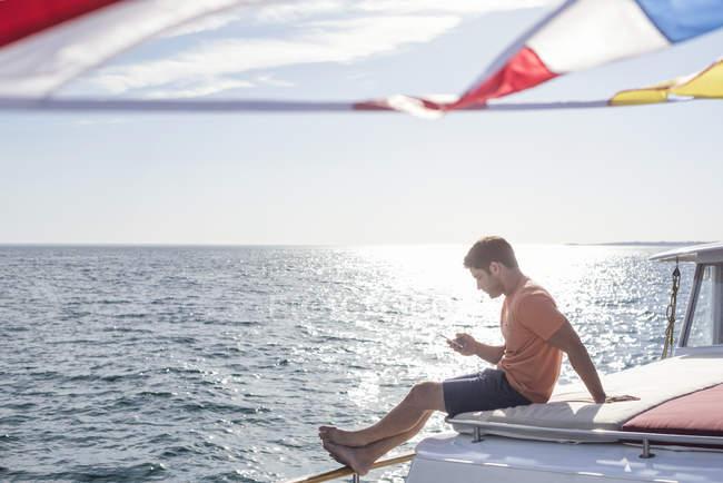 Молодой человек сидит на лодке и смотрит на сотовый телефон. — стоковое фото