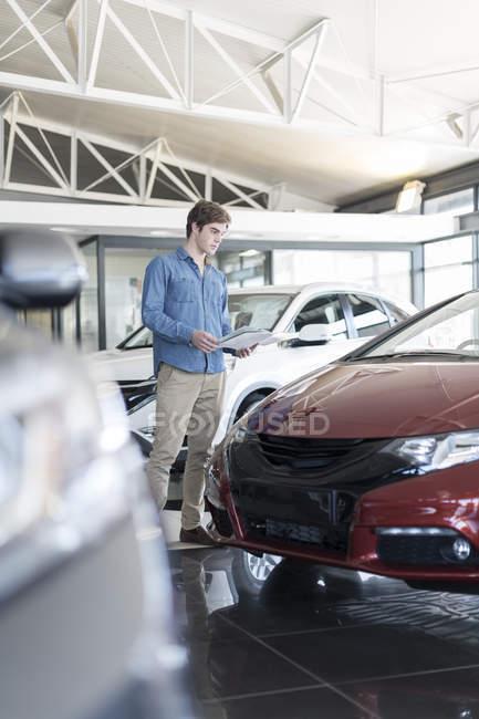 Man looking at new car at car dealership — Stock Photo