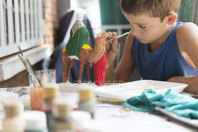 Boy painting nativity figurines — Stock Photo