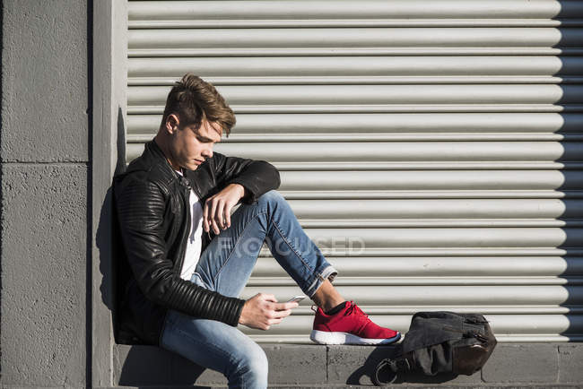 Young man sitting in niche looking at cell phone — Stock Photo